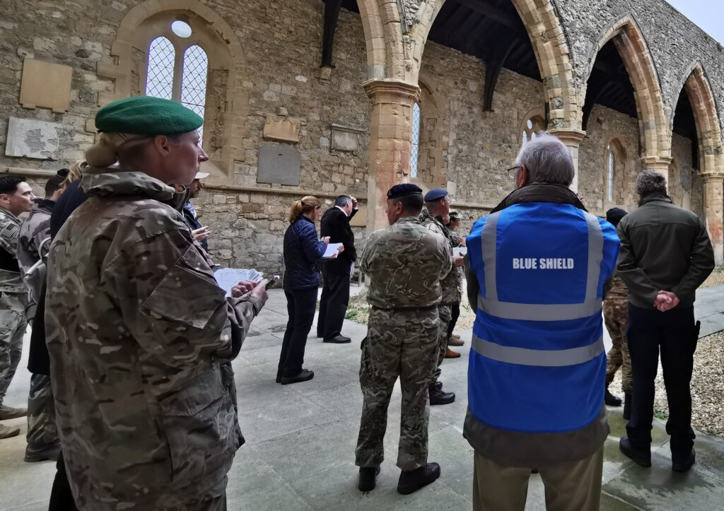 """Man in a blue high vis jacket with """"Blue Shield"""" on the back stands amongst military personnel in uniform in a historic building."""